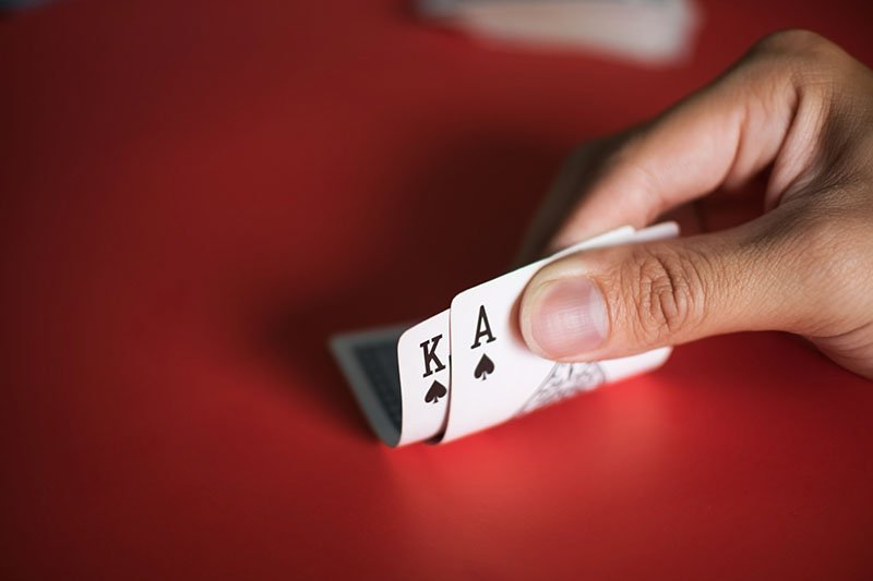 Blackjack cards in hands on red table